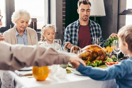 family holding hands and praying on thanksgiving