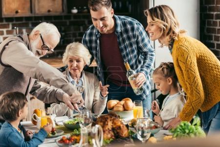 Photo pour Famille dîner de vacances et couper la dinde - image libre de droit