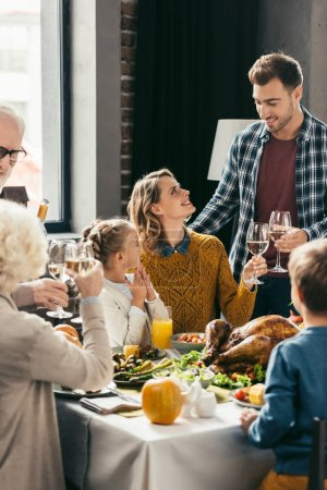 Photo for Beautiful family toasting with white wine glasses on holiday dinner - Royalty Free Image