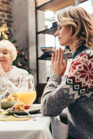 Photo pour Religieuse mère aînée et fille priant à Noël avant le dîner - image libre de droit