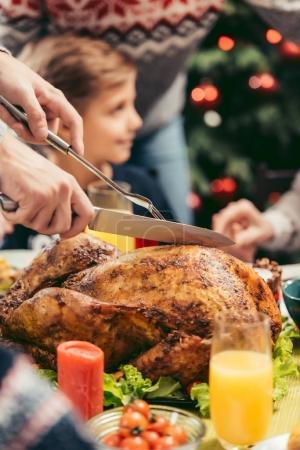 man cutting christmas turkey