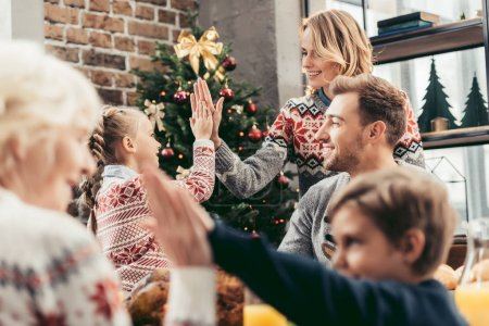Photo for Beautiful family giving high five while celebrating christmas - Royalty Free Image