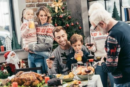 Photo pour Famille célébrant Noël ensemble tandis que grand-père verser du vin dans le verre - image libre de droit