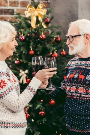 Photo pour Beau couple senior cliquetis lunettes en face de l'arbre de Noël décoré - image libre de droit