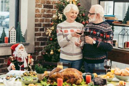 Photo pour Beau couple sénior cliquetis lunettes la veille de Noël dans la chambre décorée - image libre de droit