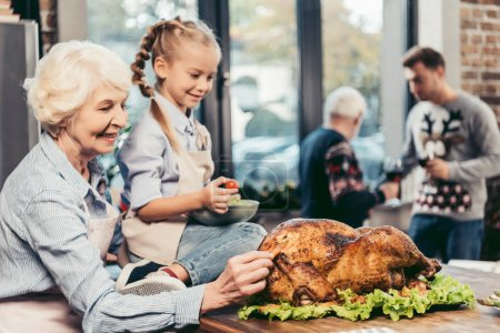 grandmother and granddaughter with turkey for holiday dinner