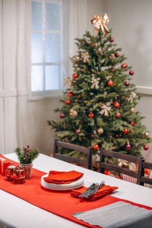 Foto de Mesa de Navidad con vajilla listo para servir en la sala de estar decorada - Imagen libre de derechos