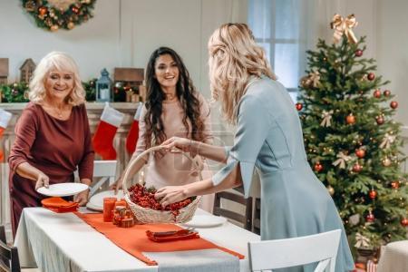 Photo pour Femmes décorant table de Noël avec leur mère aînée - image libre de droit