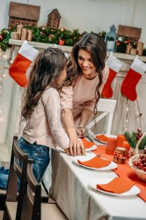mother and daughter decorating christmas table