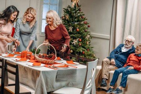 Photo pour Femmes décorant table de Noël tandis que grand-père et petit-fils assis sur le canapé - image libre de droit