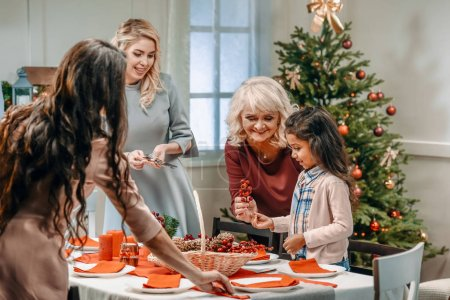 women decorating christmas table with girl