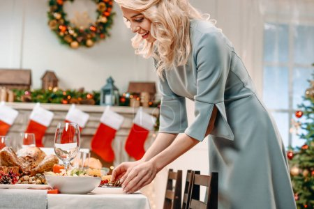 Photo for Beautiful young woman decorating christmas table - Royalty Free Image