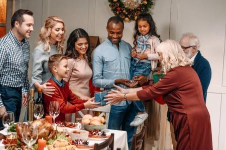 Photo pour Heureux grands-parents seniors, présentation des cadeaux à la famille nombreuse - image libre de droit
