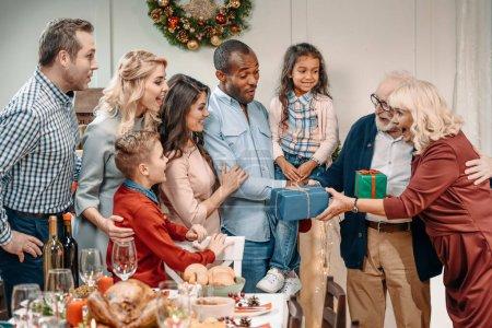Photo pour Heureux beaux grands-parents présentant des cadeaux à la grande famille - image libre de droit