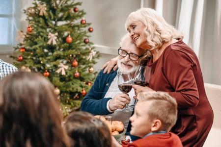 Photo pour Lunettes de tintements de couple de personnes âgées alors qu'ils célébraient Noël avec la famille - image libre de droit
