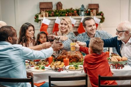Photo for Family clinking glasses while having christmas dinner - Royalty Free Image