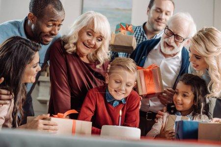 Photo pour Grande famille présenté gâteau et cadeaux aux heureux petit garçon - image libre de droit