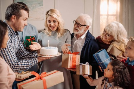 family presenting cake and gifts to woman
