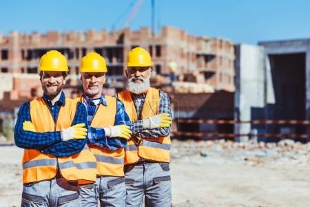 Foto de Tres trabajadores trabajo posando con los brazos cruzaron en el sitio de construcción - Imagen libre de derechos