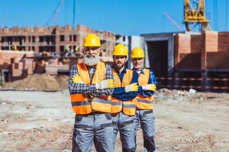 Photo pour Trois travailleurs du travail pose avec les bras croisés sur le chantier - image libre de droit