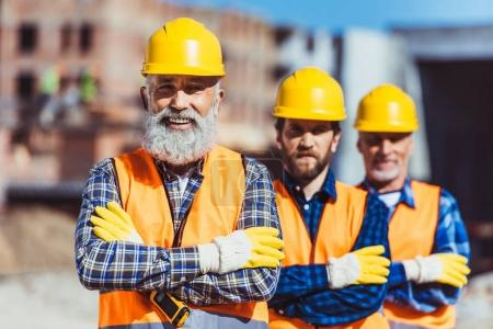 Photo for Three labour workers posing with arms crossed at the construction site - Royalty Free Image