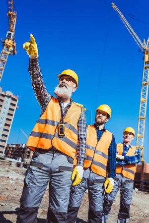 Photo pour Contremaître pointant son doigt et montrant quelque chose aux autres travailleurs sur le chantier de construction - image libre de droit