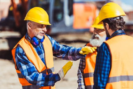 Photo pour Contremaître expliquant le processus de travail des constructeurs sur le chantier - image libre de droit