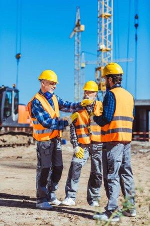 Foto de Capataz de explicar el proceso de trabajo de constructores por gesticular en el sitio de construcción - Imagen libre de derechos