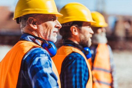 Photo for Builders in reflective vests and hardhats standing together at construction site, looking at distance - Royalty Free Image