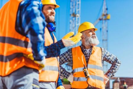Photo for Three builders in reflective vests and hardhats discussing work at construction site - Royalty Free Image