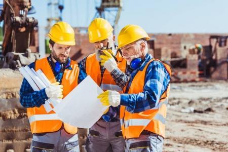 Foto de Tres trabajadores examinar planes de construcción en sitio de construcción - Imagen libre de derechos