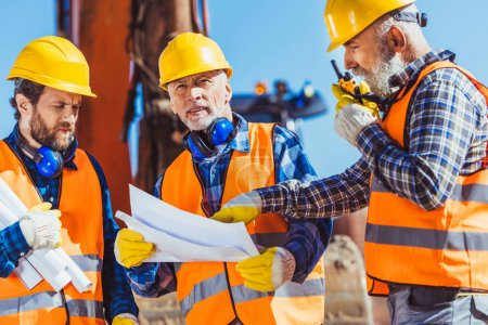 Photo for Three workers examining building plans and talking on portable radio at construction site - Royalty Free Image