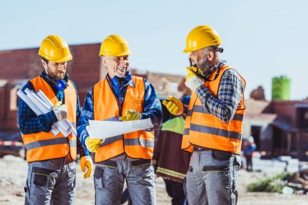 Photo for Three workers in hardhats examining building plans and talking on portable radio at construction site - Royalty Free Image