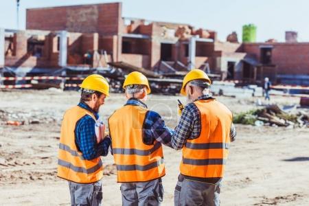 Photo pour Trois ouvriers en casques et gilets réfléchissants au chantier de construction - image libre de droit