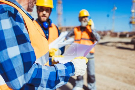Photo for Worker examining a building plan while standing at construction site with colleagues - Royalty Free Image