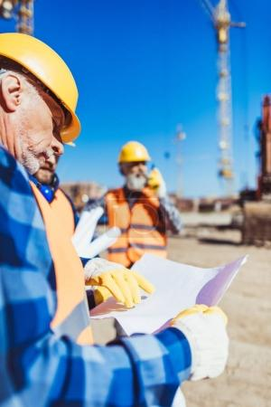 Photo for Foreman examining a building plan while standing at construction site with colleagues - Royalty Free Image