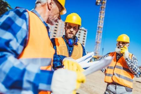 Foto de Trabajadores de cascos y chalecos examinar planes de construcción estando en sitio de construcción - Imagen libre de derechos