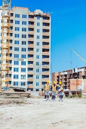 Photo pour Trois constructeurs en casques et gilets marchant vers la caméra sur le chantier - image libre de droit