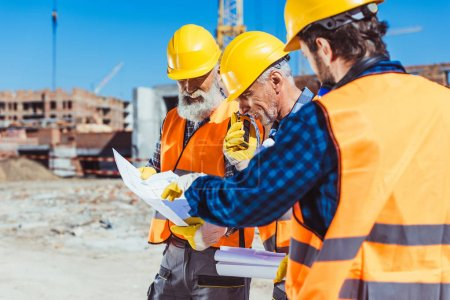 Photo for Three workers in reflective vests and hardhats standing at construction site and examining building plans - Royalty Free Image