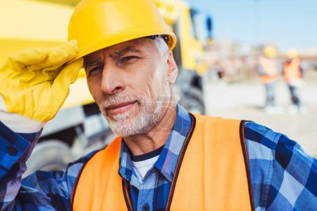Photo for Portrait shot of worker in reflective vest adjusting his hardhat and looking at camera - Royalty Free Image