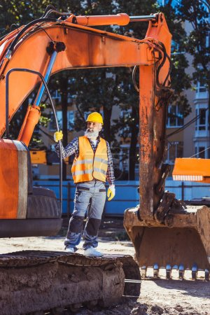 Construction worker posing with excavator