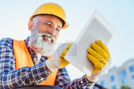 Photo pour Ouvrier du bâtiment souriant en veste réfléchissante et casque à l'aide de tablette numérique - image libre de droit