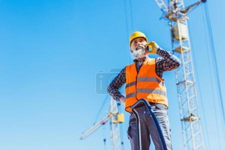 Photo pour Travailleur de la construction souriant en gilet réfléchissant et casque dur parlant sur smartphone - image libre de droit