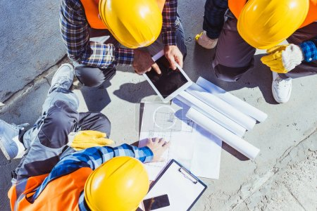 Photo for Three construction workers sitting on concrete and discussing building plans - Royalty Free Image