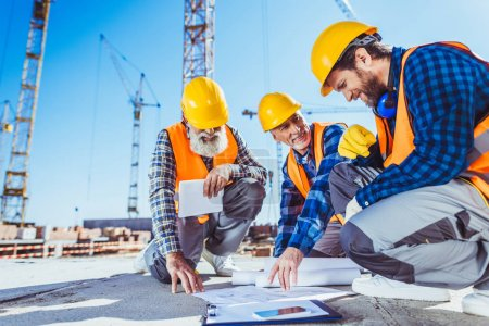 Photo for Three construction workers sitting on concrete at construction site, discussing building plans - Royalty Free Image