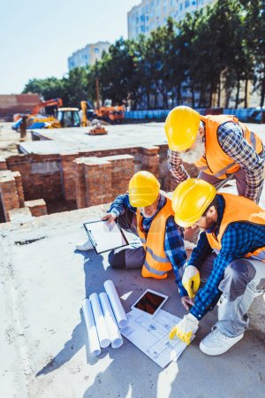 Photo for Three construction workers in hardhats sitting on concrete at construction site, examining building plans - Royalty Free Image