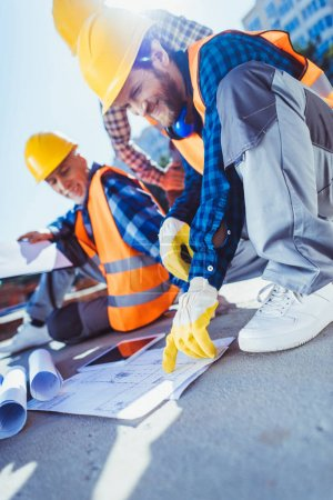 Photo for Smiling construction workers in hardhats sitting on concrete at construction site, examining building plans - Royalty Free Image