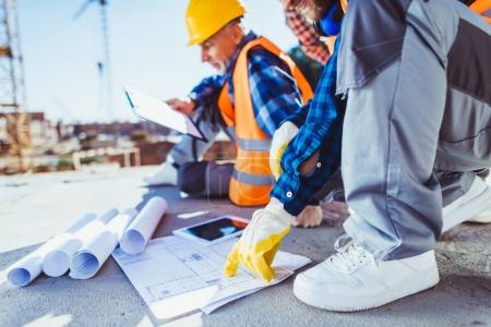 Photo for Cropped shot of construction workers in uniform sitting on concrete at construction site, examining building plans - Royalty Free Image
