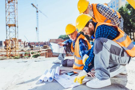 Photo for Construction workers in uniform sitting on concrete at construction site, discussing building plans - Royalty Free Image