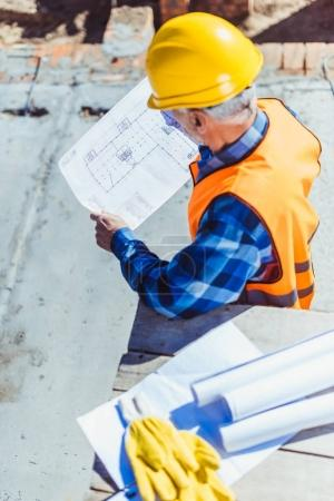 construction worker examining building plans